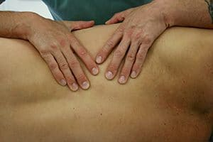 Idris is operformig a deep tissue massage treatment on a patient in his Natural Moves Studio in Notting Hill, London W10