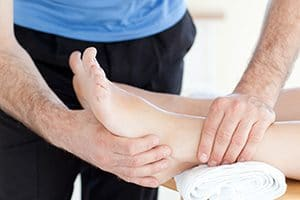 Idris is operformig a deep tissue massage treatment on a male foot in his Natural Moves Studio in Notting Hill, London W10
