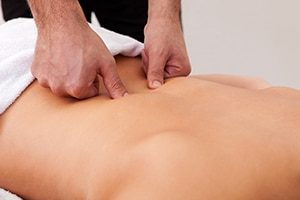 Idris is operformig an osteopathic treatment on a white male patient in the Natural Moves Studio in Notting Hill, close to Ladbroke Grove, London W10