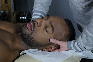 Idris is operformig an osteopathic treatment on a black patient in the Natural Moves Studio in Notting Hill, close to Ladbroke Grove, London W10