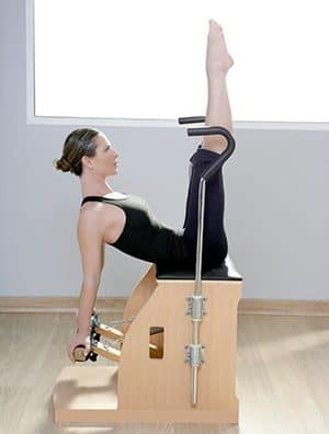 Idris is instructing a client on a Pilates Wunda chair in the Natural Moves Studio in Notting Hill, London W10