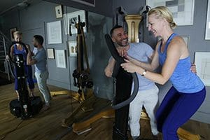 Idris is instructing a client on a Vibration training machine in the Natural Moves Studio in Notting Hill, London W10